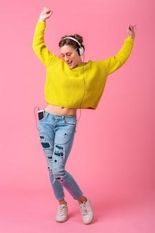 Atrakcyjna kobieta szczęśliwy zabawny taniec, słuchanie muzyki w słuchawkach, ubrana w strój kolorowy styl hipster na białym tle na tle różowego studia