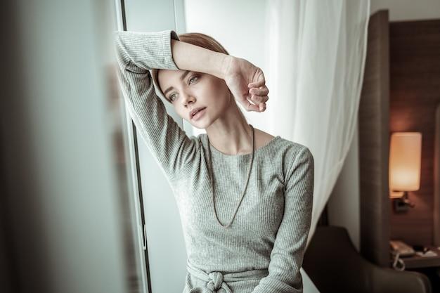 Atrakcyjna kobieta. szczupła, atrakcyjna blondyneczka siedząca przy oknie w swoim przestronnym, jasnym mieszkaniu