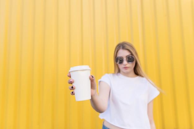 Atrakcyjna kobieta trzyma białą filiżankę kawy w jej ręce na żółtej ścianie. skoncentruj się na filiżance