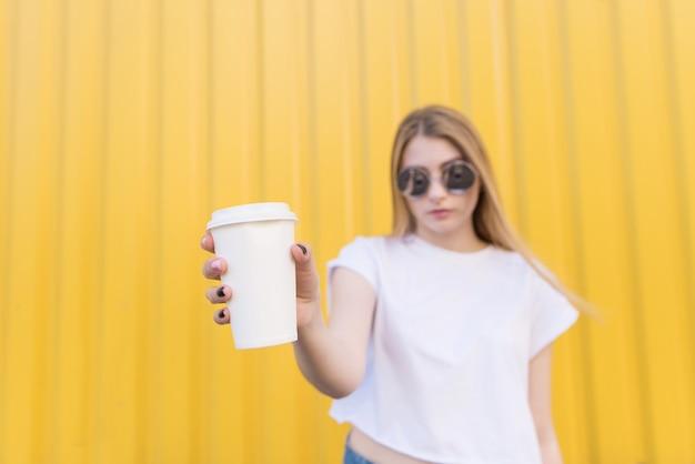 Atrakcyjna kobieta trzyma białą filiżankę kawy w jej ręce na żółty