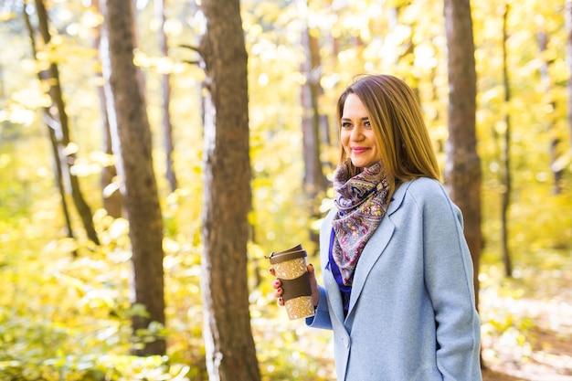Atrakcyjna kobieta trzyma filiżankę filiżanki kawy na wynos na ulicy jesień