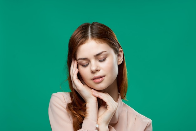 Atrakcyjna kobieta trzyma rękę w pobliżu twarzy emocji pasja modelu zielonym tle. wysokiej jakości zdjęcie