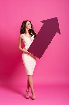Atrakcyjna kobieta trzyma różowy znak strzałki