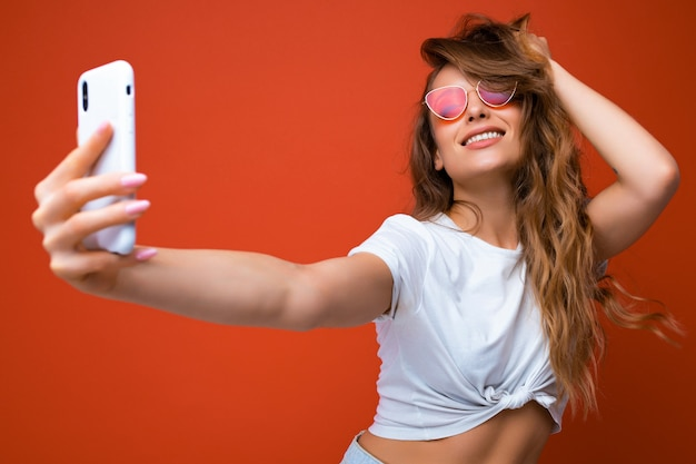 Atrakcyjna kobieta trzyma telefon komórkowy i używa go