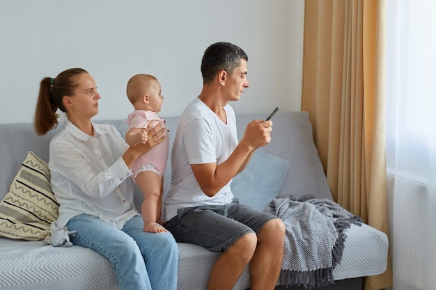 Atrakcyjna kobieta trzymająca w rękach córeczkę, jej mąż siedzący tyłem do rodziny i korzystający ze smartfona, nie chce spędzać czasu z bliskimi ludźmi, surfować po internecie czy pisać wiadomości.