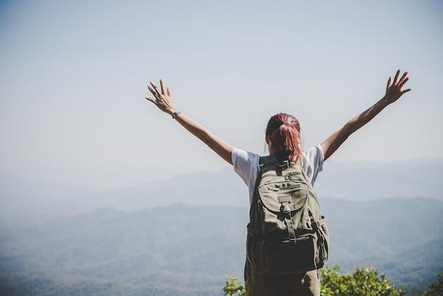 Atrakcyjna kobieta turysta otwarte ramiona na szczycie góry, cieszyć się naturą. koncepcja podróży.