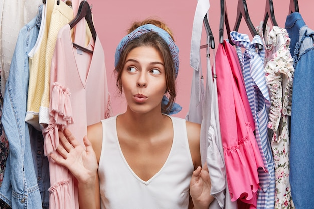 Atrakcyjna kobieta ubrana niedbale, patrząc na bok z wątpliwościami stojąc obok wieszaków z ubraniami, zastanawiając się, w co się ubrać na spotkaniu biznesowym z towarzyszami. kobieta mody o wiele ubrań