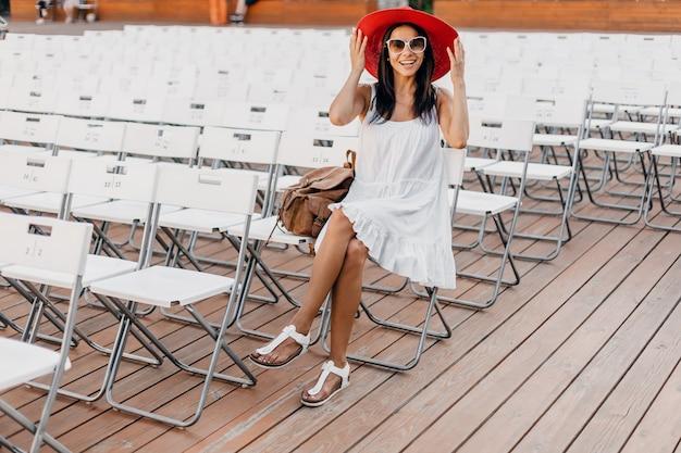 Atrakcyjna kobieta ubrana w białą sukienkę, czerwony kapelusz, okulary przeciwsłoneczne siedząca w letnim teatrze na świeżym powietrzu na samym krześle, wiosenny trend w modzie ulicznej, dystans społeczny