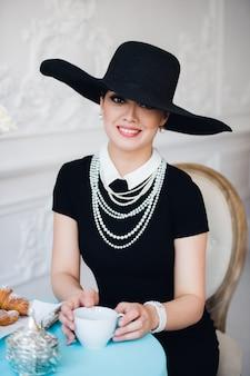Atrakcyjna kobieta ubrana w czarną sukienkę, kapelusz i perły, siedząc na krześle