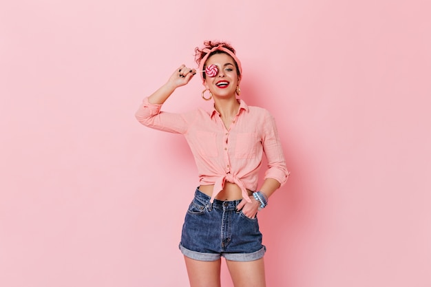 Atrakcyjna kobieta ubrana w koszulkę pin-up i opaskę pozuje z lizakiem na różowej przestrzeni.