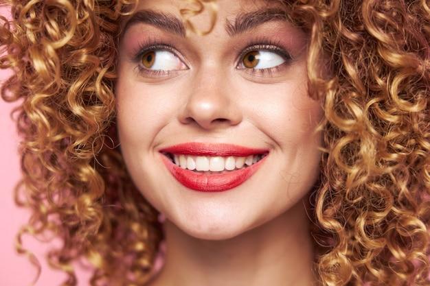 Atrakcyjna kobieta uśmiechnięte czerwone usta kręcone włosy model jasny makijaż