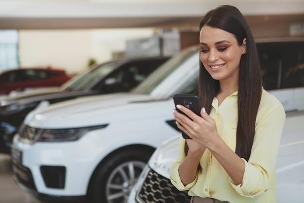 Atrakcyjna kobieta używa jej mądrze telefon podczas gdy bying nowego samochód