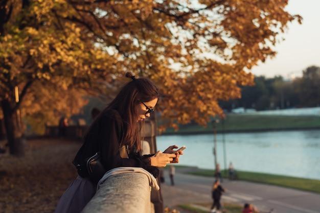 Atrakcyjna kobieta używa smartphone outdoors w parku