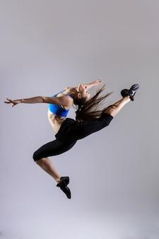 Atrakcyjna kobieta w akwamaryn sportowej z kucykiem, pracuje na szarym tle
