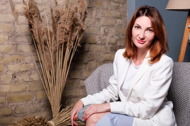 Atrakcyjna kobieta w białej eleganckiej kurtce kobieta siedzi na krześle i patrzy w kamerę