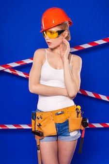 Atrakcyjna kobieta w białej koszuli, pasie, kasku, okularach, szortach jeansowych i snickers