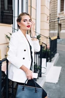 Atrakcyjna kobieta w białej kurtce jest oparta na płocie na ulicy. ona patrzy do kamery.