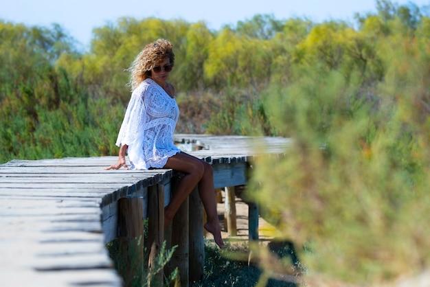 Atrakcyjna kobieta w białej sukni siedzi boso na podwyższonej kładce prowadzącej w kierunku naturalnego lasu. kobieta w białej sukni i okularach przeciwsłonecznych relaksuje się na podwyższonym drewnianym moście pośród zielonego lasu