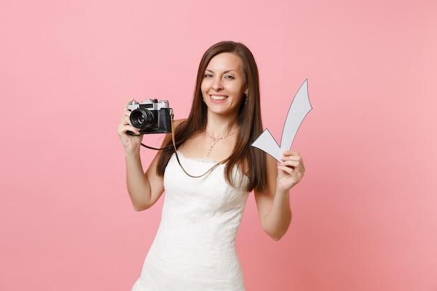 Atrakcyjna kobieta w białej sukni trzymająca aparat retro vintage i znacznik wyboru, wybierająca personel, fotograf