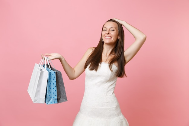 Atrakcyjna kobieta w białej sukni trzymająca rękę na głowie trzymająca wielokolorowe torby z zakupami po zakupach
