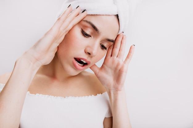 Atrakcyjna kobieta w białym ręczniku ma ból głowy. migawka dziewczyny ze zdrową skórą na odizolowanej ścianie.