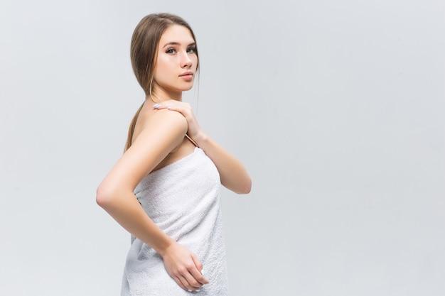 Atrakcyjna kobieta w białym ręczniku po pchnięciu i pozowaniu