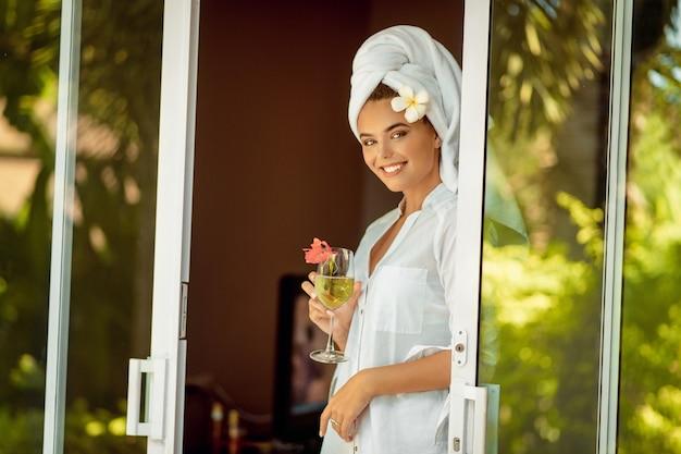Atrakcyjna kobieta w białym szlafroku i ręcznik trzyma kieliszek do szampana i kwiat