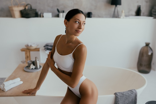 Atrakcyjna kobieta w bieliźnie pozowanie w pobliżu wanny. dziewczyna pozuje do kamery