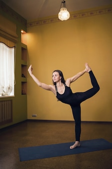 Atrakcyjna kobieta w czarnej pełnej długości sportowej praktykuje jogę w studio wykonując ćwiczenia natarajasana lub pozie króla tancerzy