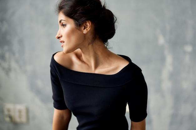 Atrakcyjna kobieta w czarnej sukni dekoracji pozowanie zbliżenie