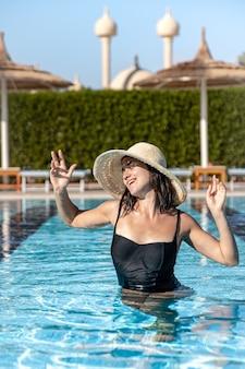 Atrakcyjna kobieta w czarnym stroju kąpielowym i kapeluszu kąpie się w basenie.