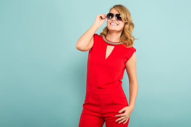 Atrakcyjna kobieta w czerwonych kombinezonach i okularach przeciwsłonecznych