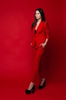 Atrakcyjna kobieta w czerwonym garniturze i czarnych szpilkach