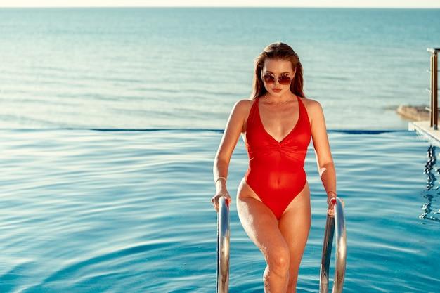 Atrakcyjna kobieta w czerwonym stroju kąpielowym i okulary przeciwsłoneczne wychodzi z basenu