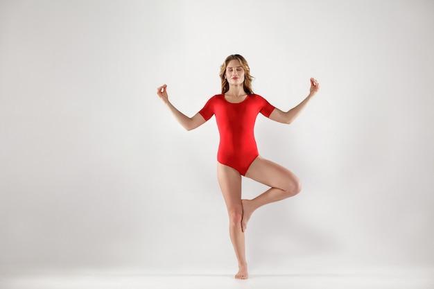 Atrakcyjna kobieta w czerwonym trykocie stojąca na jednej nodze i robiąca drzewo jogi