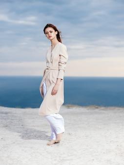 Atrakcyjna kobieta w eleganckim stylu latem płaszcz piasek. zdjęcie wysokiej jakości