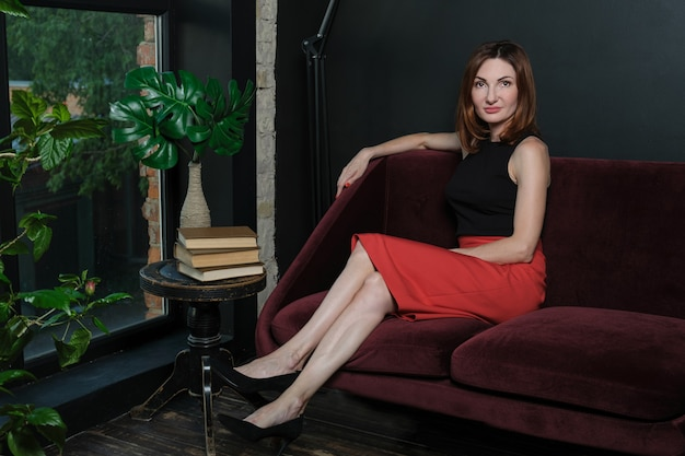 Atrakcyjna kobieta w jaskrawoczerwonej spódnicy i czarnej bluzce bez rękawów siedzi na kanapie w biurze
