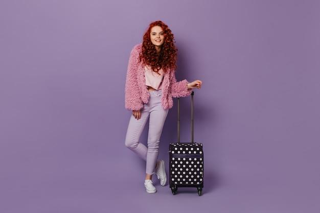 Atrakcyjna kobieta w jasnych spodniach, różowym krótkim płaszczu i bluzce, słodko uśmiechnięta, oparta na walizce.