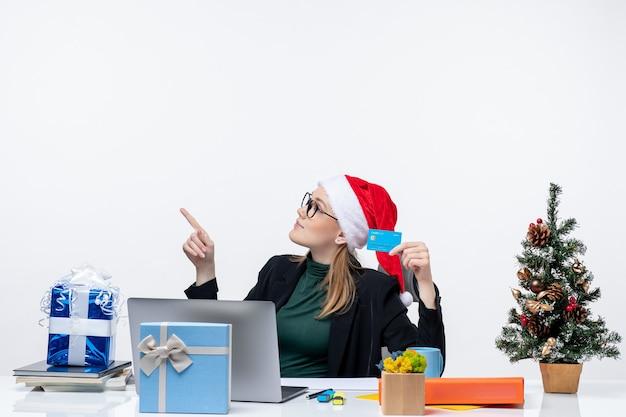 Atrakcyjna kobieta w kapeluszu świętego mikołaja i okularach siedzi przy stole prezent na boże narodzenie i trzymając kartę bankową w materiałach biurowych