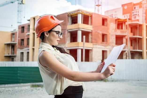 Atrakcyjna kobieta w kasku konstruktora patrząc na plan