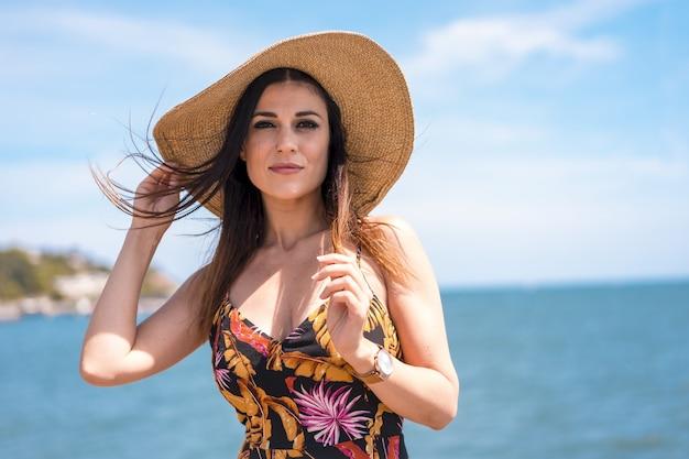 Atrakcyjna kobieta w kwiecistej sukience i kapeluszu schwytana przez ocean w san sebastian, hiszpania