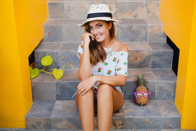 Atrakcyjna kobieta w lecie uśmiechnięta na sobie słomkowy kapelusz, siedząc boso w drukowanej koszulce letnie wakacje mody