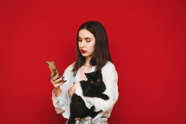 Atrakcyjna kobieta w lekkie ubranie stoi z kotem w dłoniach
