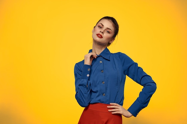 Atrakcyjna kobieta w niebieskiej koszuli gestykuluje z rękami i czerwoną spódnicą na żółtym tle