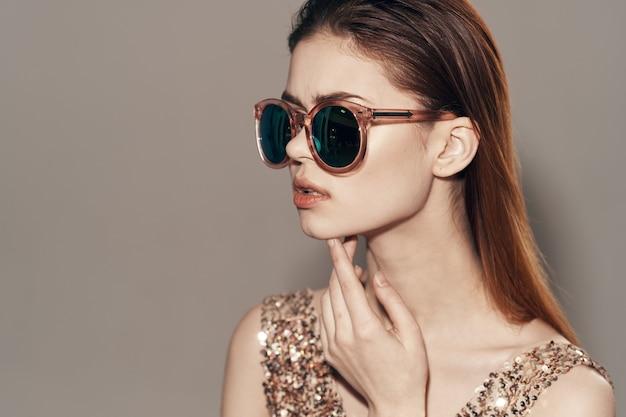 Atrakcyjna kobieta w okularach przeciwsłonecznych w złotej sukience modelka studio model