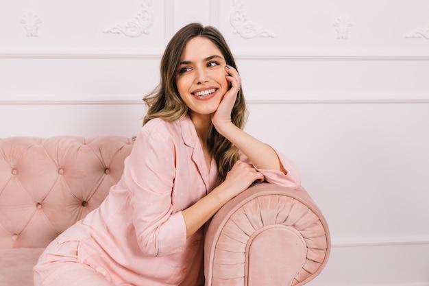 Atrakcyjna kobieta w piżamie siedzi na kanapie