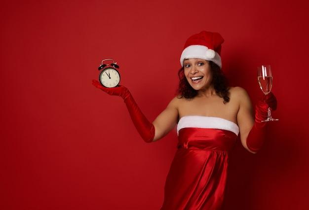 Atrakcyjna kobieta w santa hat i santa dress trzyma flet szampana z winem musującym i budzikiem, uśmiecha toothy uśmiech pozowanie na kolorowym tle, kopia przestrzeń. boże narodzenie, szczęśliwego nowego roku