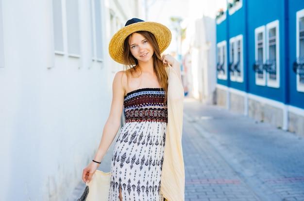 Atrakcyjna kobieta w słomkowym kapeluszu i sukience podróżuje ulicą