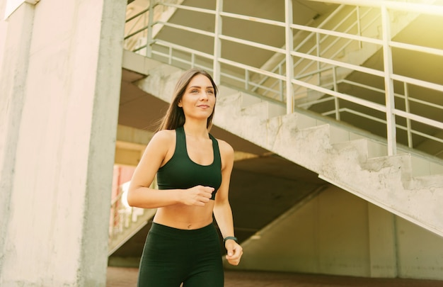 Atrakcyjna kobieta w sportowej działa na zewnątrz w środowisku miejskim