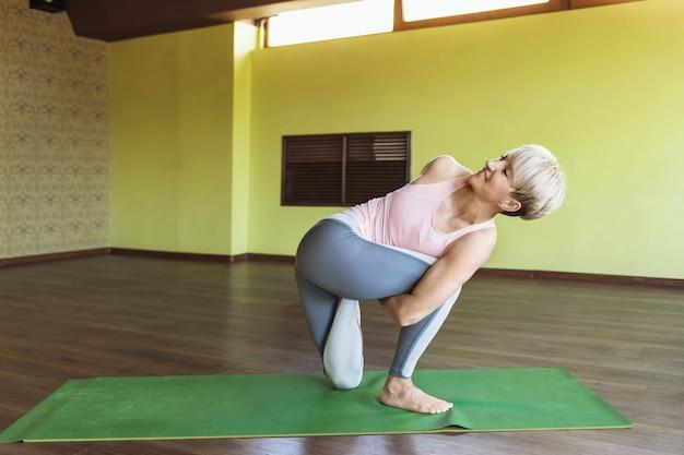 Atrakcyjna kobieta w sportowych legginsach i podkoszulku trenuje w studio